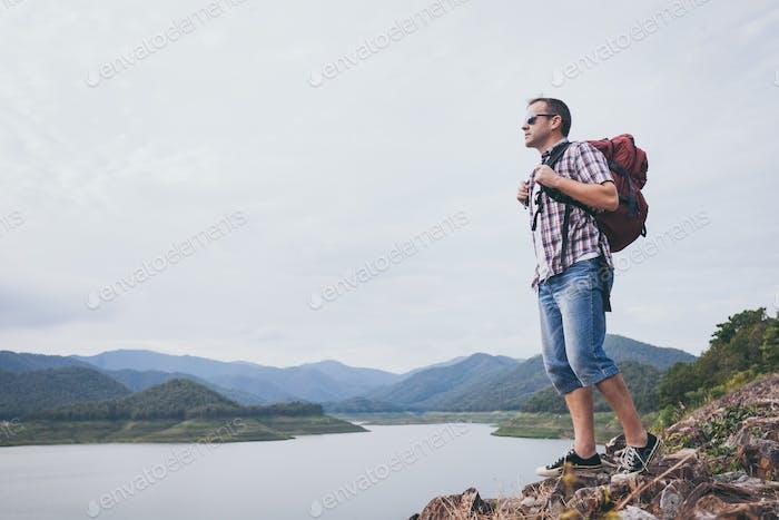 Glücklicher Mann, der in der Nähe des Sees zur Tageszeit steht.