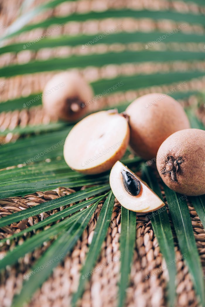 Sapodilla or ciku fruit over palm leaves on rattan background. Copy space. Dimocarpus longan. Bunch