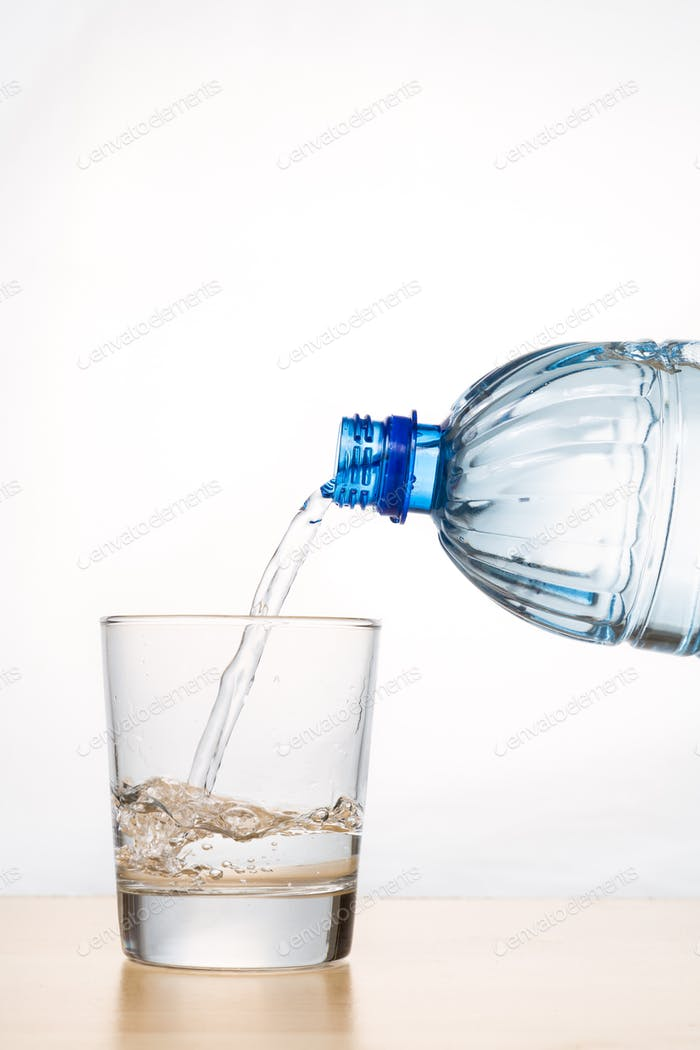 Vertical shot of hand pouring water from bottle into glass