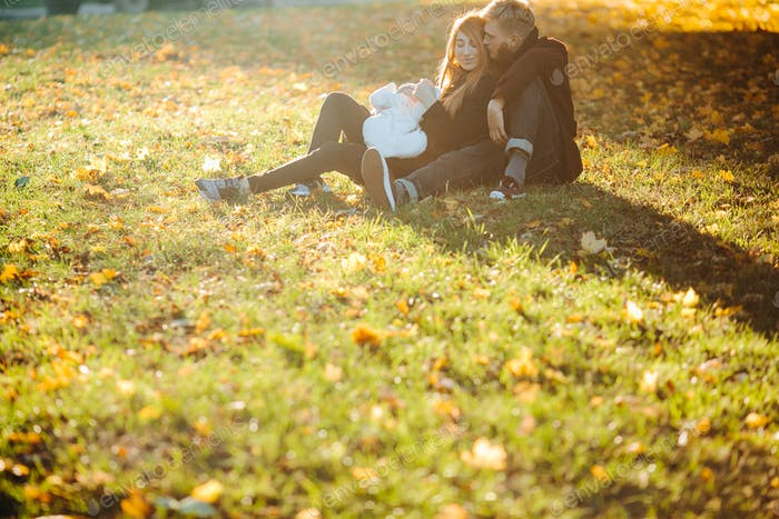young family and newborn son in autumn park