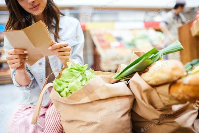 Frau liest Einkaufsliste im Geschäft