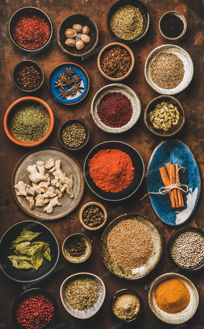 Flat-lay of various spices in bowls over rusty background