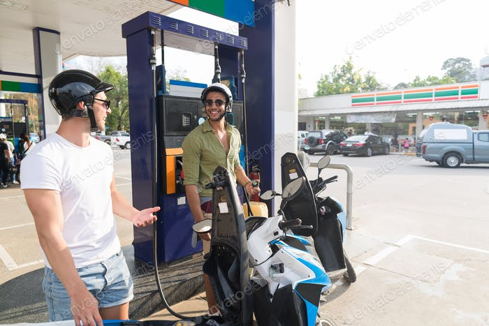 Mann Paar auf Tankstelle Kraftstoff Motorrad, glücklich lächelnd Jungs Reisen