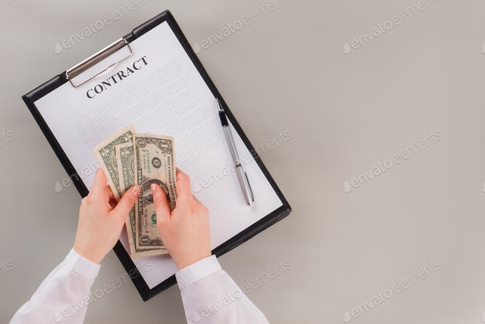 Business woman counting money on table with contract.
