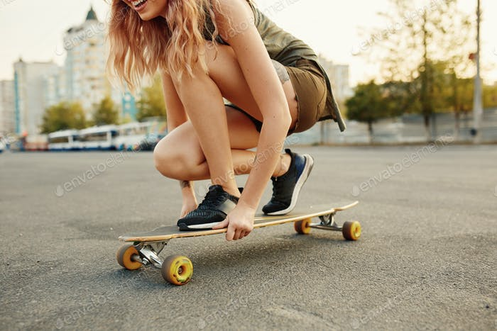 Beautiful young girl with tattoos sits on longboard