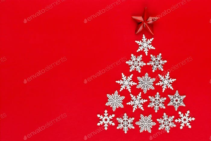 Christmas tree made from white snow flake decorations on red  background.