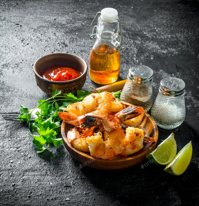 Spicy shrimps in a bowl with slices of lime, parsley and sauce.