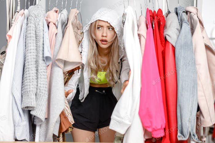 Funny young girl blogger dressed in fashionable clothes standing between clothes hanging on a hanger