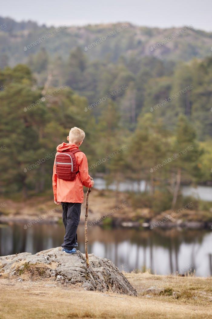 A boy standing on a rock admiring a view of lake, back view, Lake District, UK