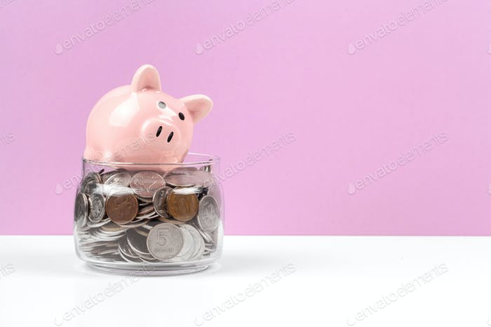alcancía con moneda sobre la mesa