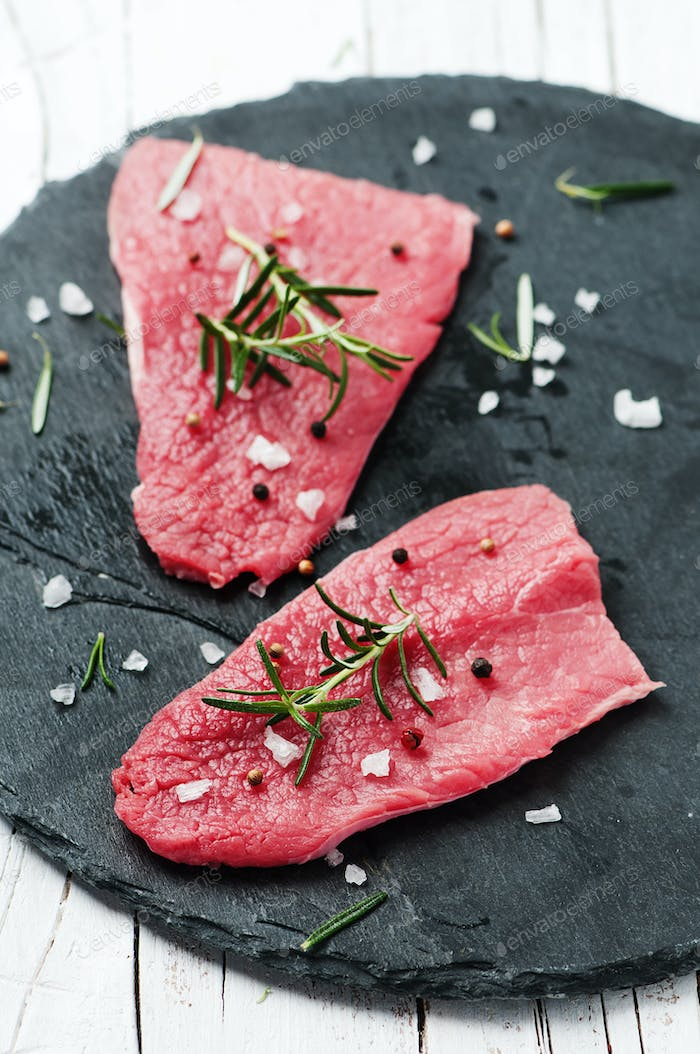 Uncooked meat with rosemary and salt