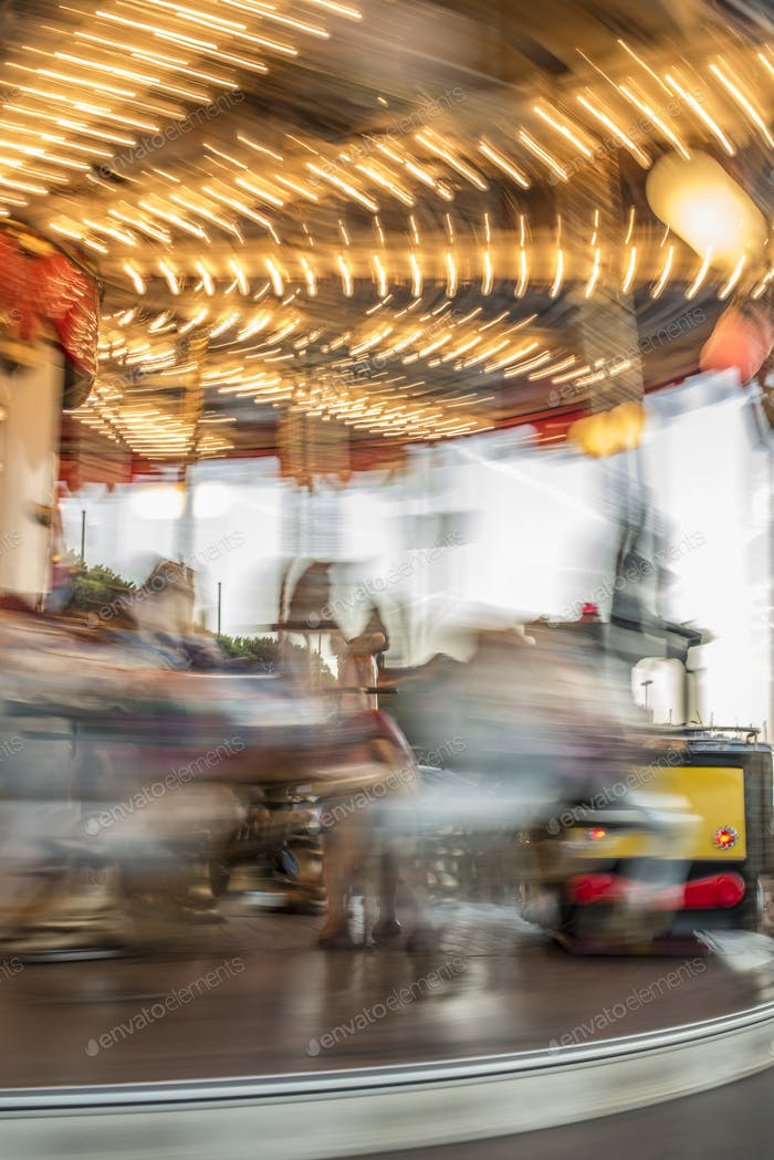 Carousel with horses in amusement park.