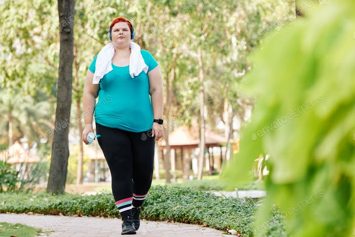 Overweight woman walking in park