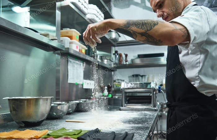 Handsome young chef with black tattoos on his arms pouring flour on kitchen table making pasta