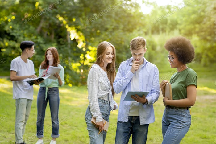 Multi-ethnic group of students spending time together outdoors at college campus