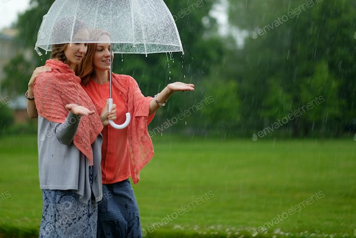 Two women walking park in rain and talk. Friendship and people communication.