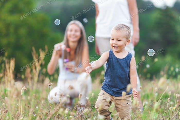Glückliches Kind mit Familie mit einer großen Zeit Blasen Blasen