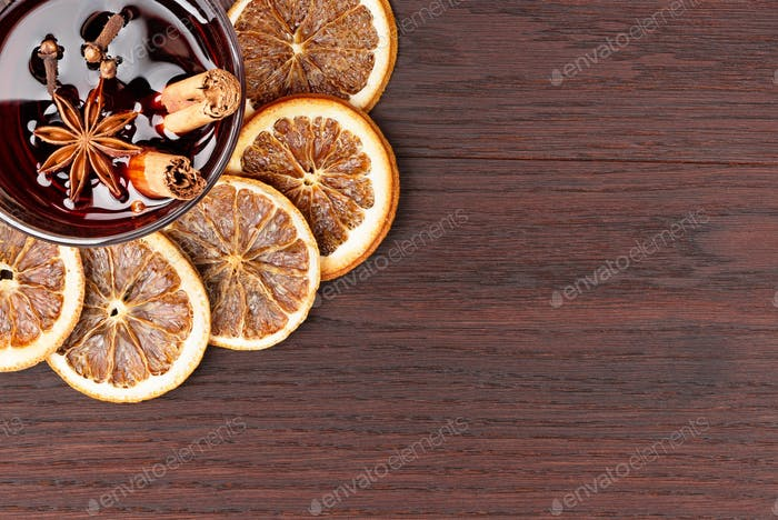 mulled wine and orange slices on wooden background