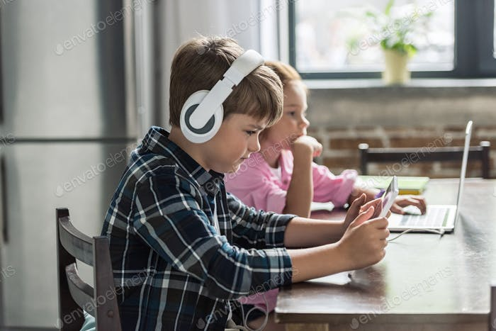little brother and sister using digital devices at home