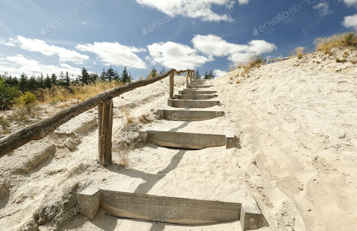 stairs on sand to blue sky with clouds
