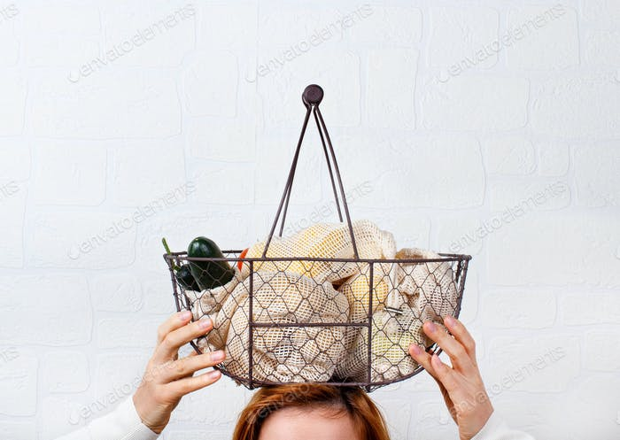 Woman keeps backet with fresh vegetables and fuits  in textile bags