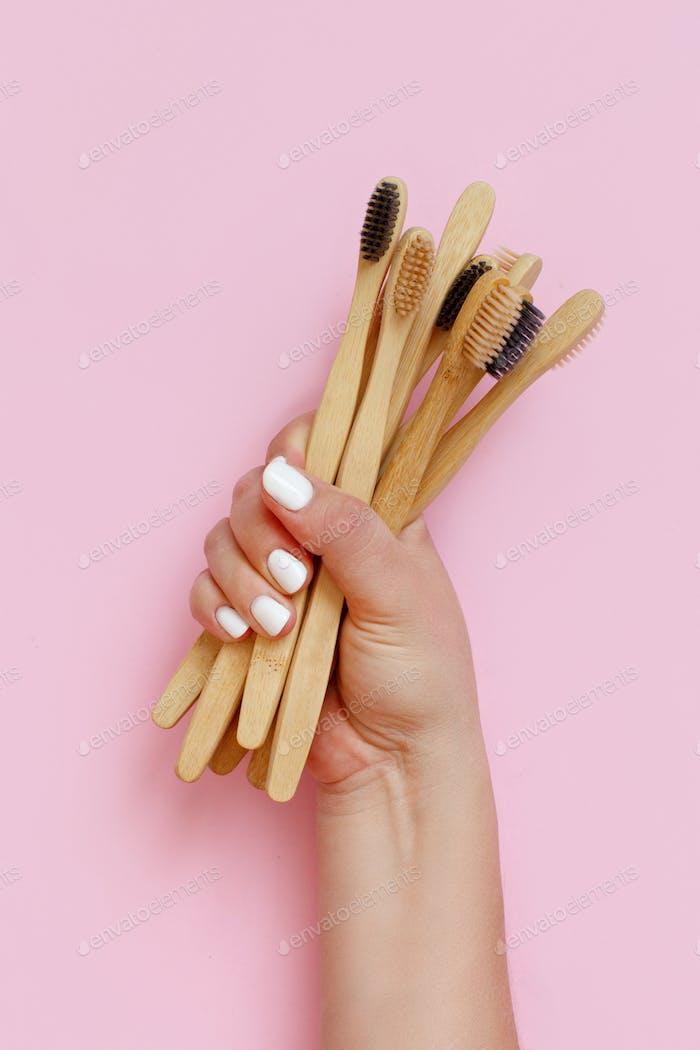 Hand hält umweltfreundliche Bambuszahnbürsten auf rosa Hintergrund