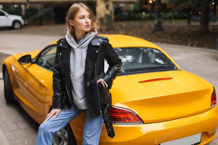 Young beautiful woman in leather jacket leaning on yellow sport