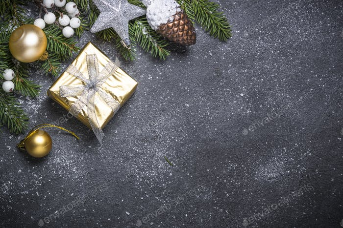 Gold present box and decorations on black stone background