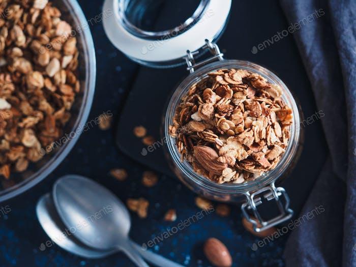 Homemade granola in glass jar on dark table