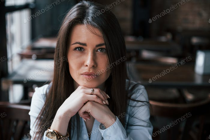 Focused photo. Businesswoman in official clothes is indoors in cafe at daytime
