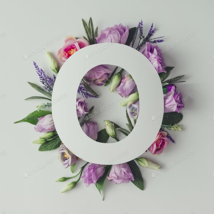 Creative layout with colorful flowers, leaves and letter O. Love concept.Flat lay.