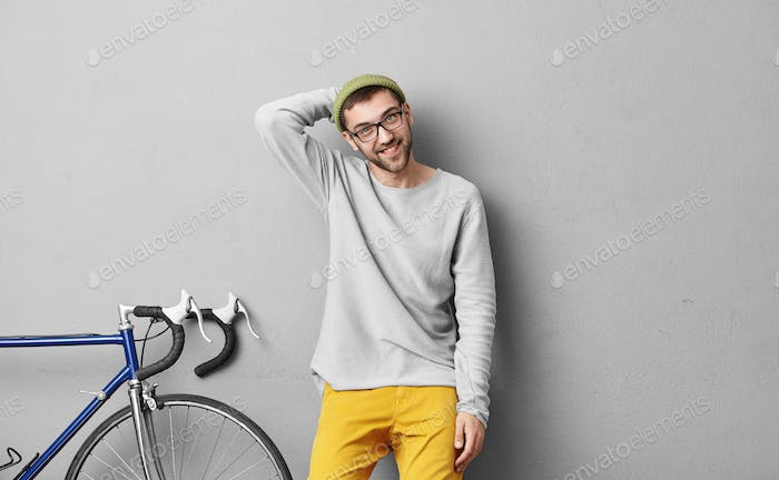 Cheerful unshaven guy in hat and oversized sweater being glad after having cycle race. Unshaven raci