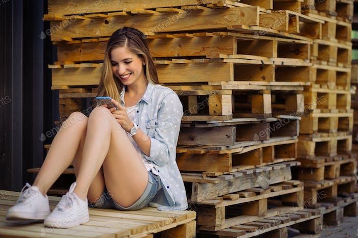 Charmantes Mädchen sitzt auf einer Palette mit Smartphone