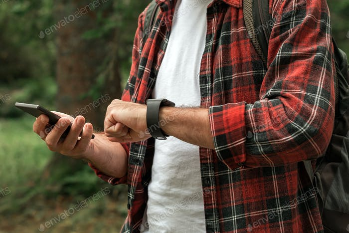 Hiker connecting smartwatch to smartphone to synchronize the data