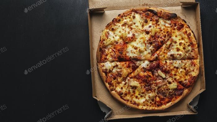 Pizza with salami and cheese on pizza box