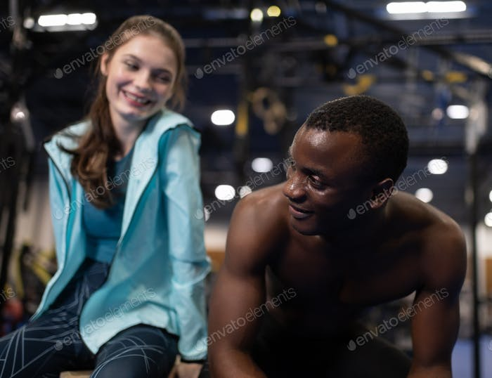 Sportive couple talking and flirting after training in gym