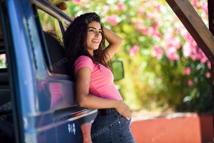 Young woman in a camper van in a beautiful camping with pink flowers