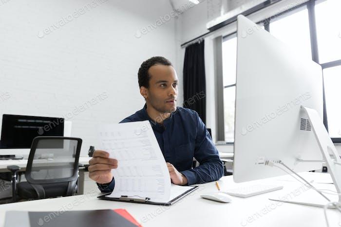 Junge afrikanische Geschäftsmann sitzt an seinem Schreibtisch