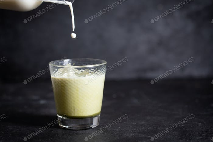 Hot Green matcha latte with almond milk on a black background with copy spase