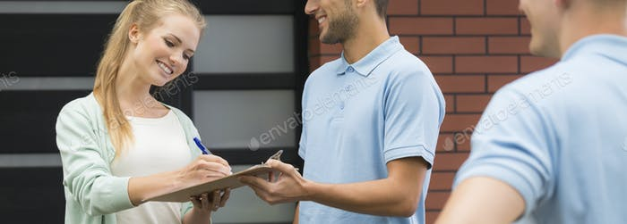 Young woman signing the delivery sheet