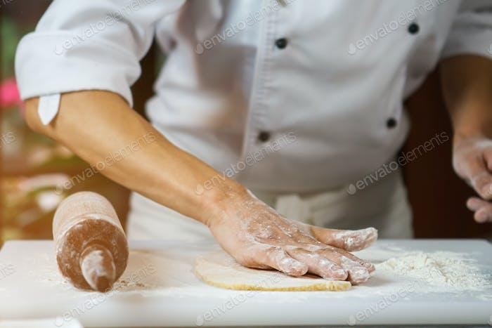 Male hands touching dough