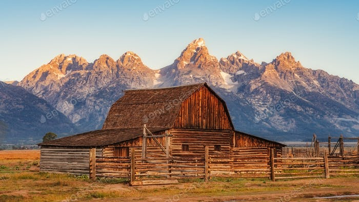 Landscape view of Grand Teton mountain range and abandoned barn, USA
