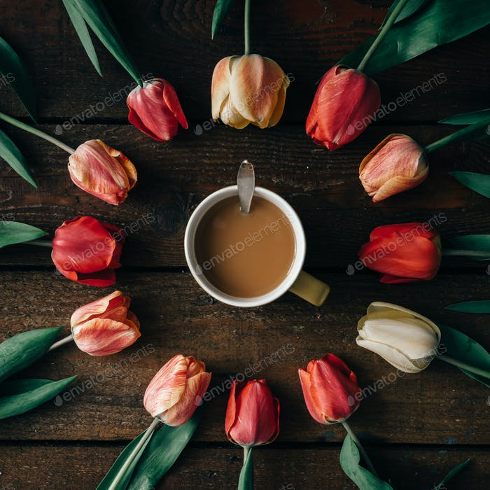 Coffee cup with creative arrangement of tulips  on wooden background