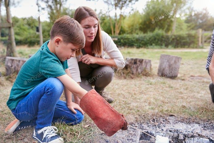 Weibliche Teamleiter mit Jungen auf Outdoor-Aktivität Reise Toasten Marshmallows über Lager Feuer