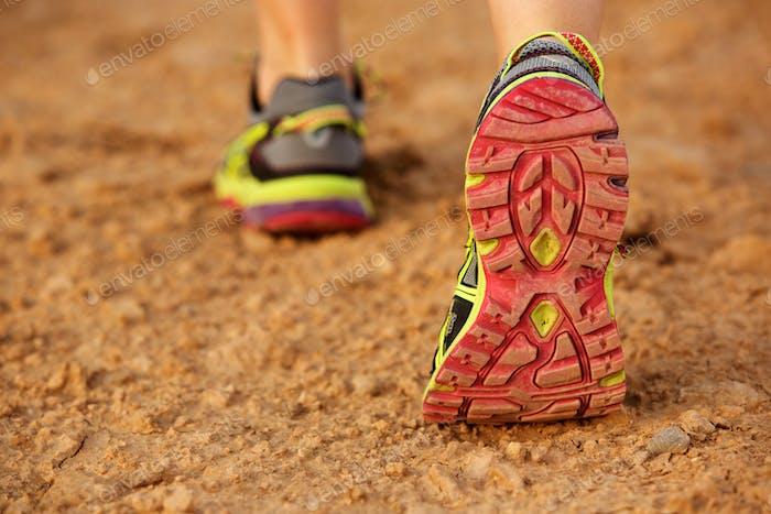 Rückseite des weiblichen Schuhs zu Fuß auf unbefestigte Straße