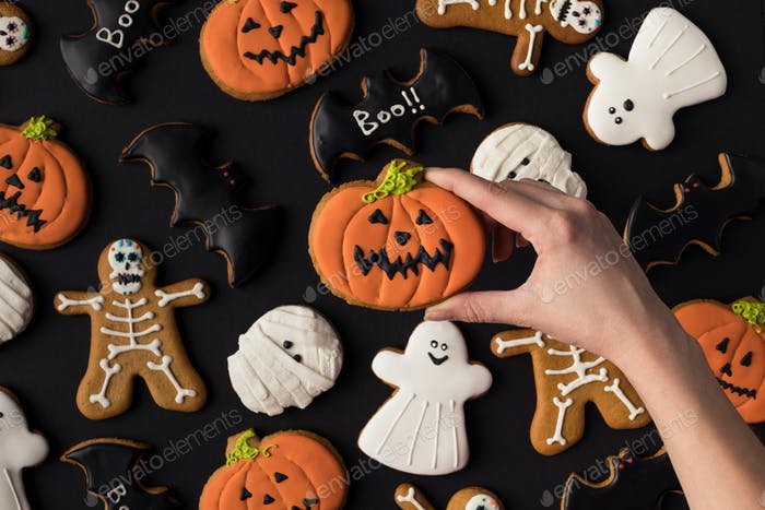 abgeschnittene Schuss menschlicher Hand und verschiedene dekorative Halloween-Kekse