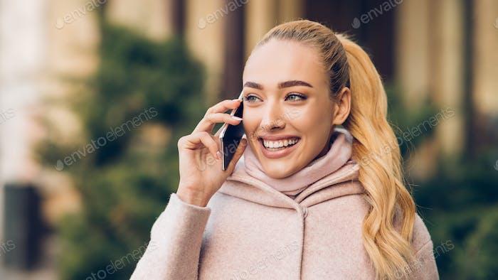 Millennial Frau im Gespräch am Telefon im Freien, warten auf Freund