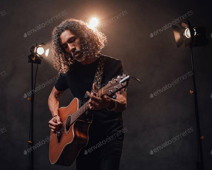 Talanted hispanischen Musiker spielen Gitarre in Bühnenlichtern