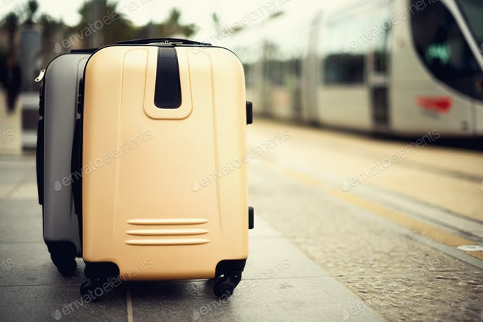 Two suitcases standing on railway station against city train. Vacation and travel concept. Citypass