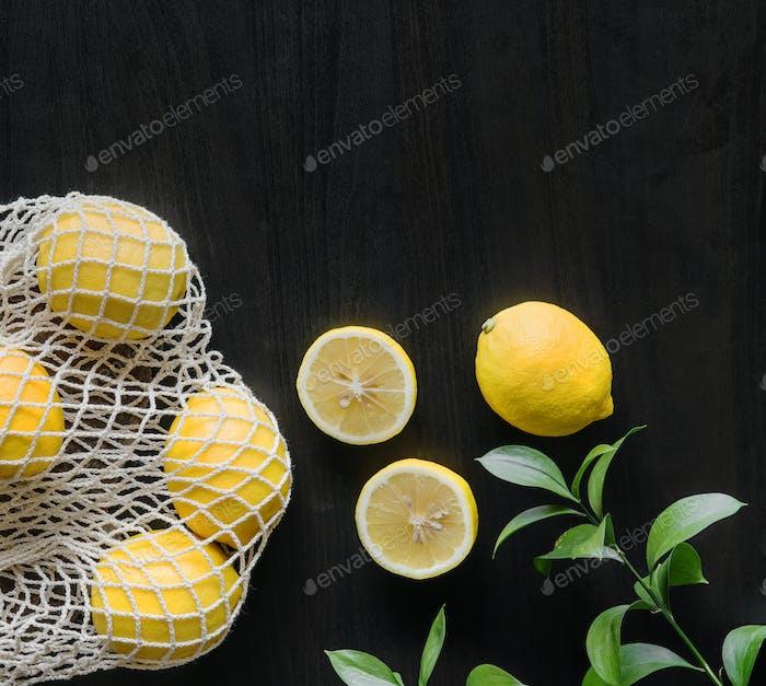 Свежие желтые лимоны на черном фоне